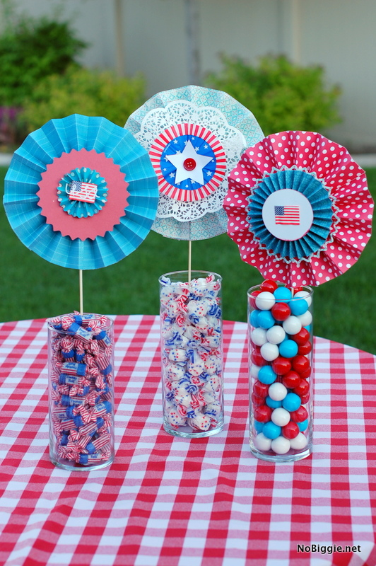 Here's a simple festive way to decorate for a patriotic party this Summer. Fill big glass vases with festive red white and blue candy and top them off with these accordion folded paper medallions, or paper